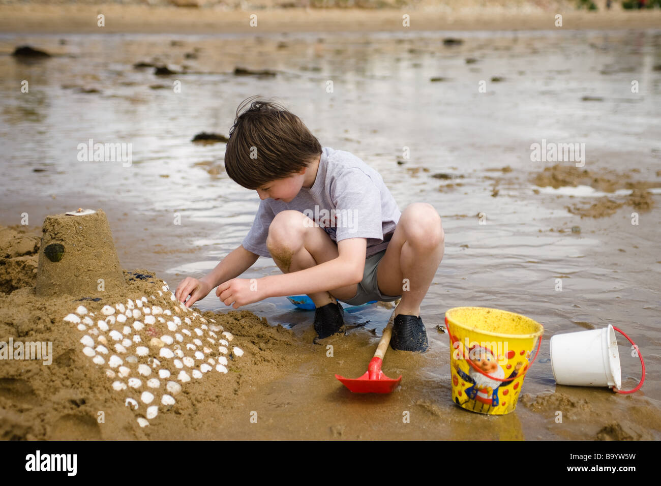 A pre-teen boy bends over to decorate his sand castle with white shells with plastic toys and reflecting water in - Stock Image