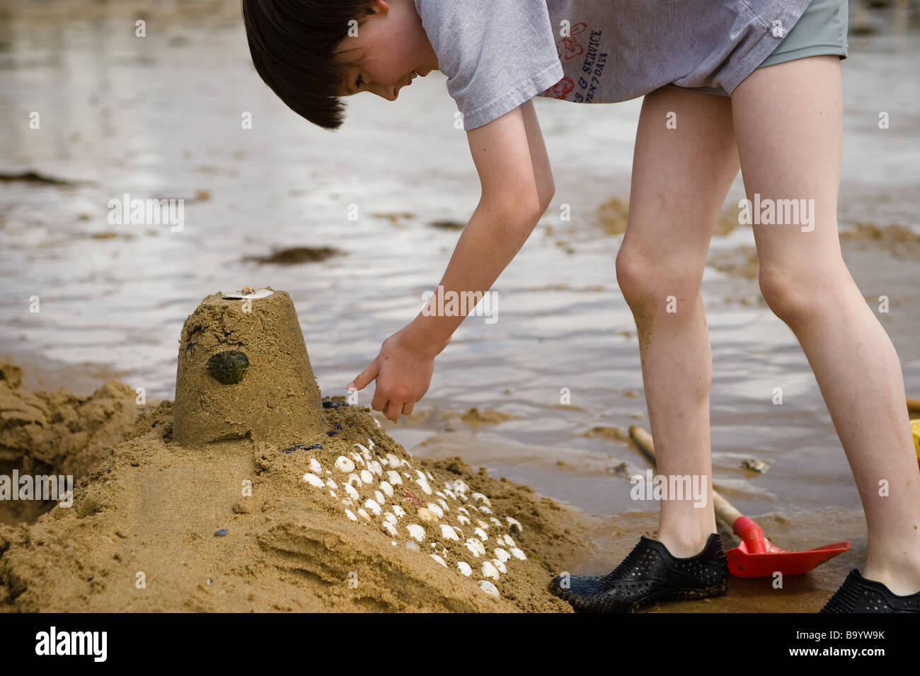 A pre-teen boy bends over to decorate his sand castle with white shells with a red shovel and reflecting water in - Stock Image