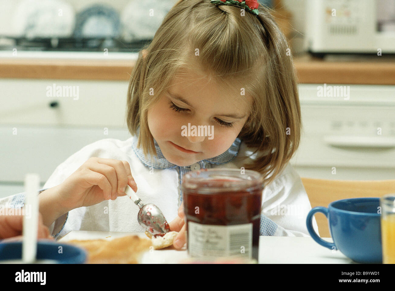 Girl putting jam on bread - Stock Image