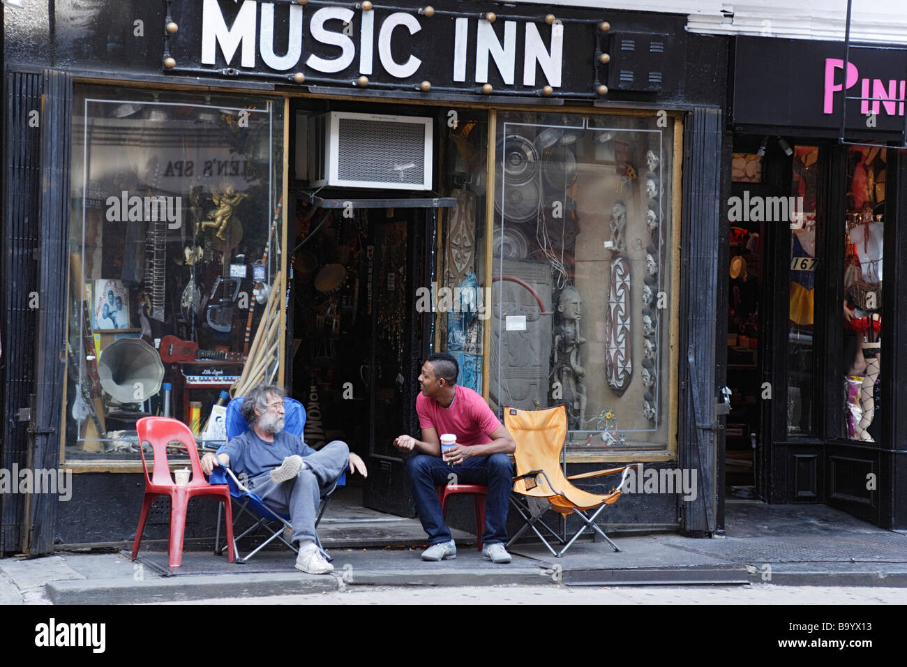 Two men sitting in front of a music store Greenwich Village Manhattan New York City New York USA - Stock Image