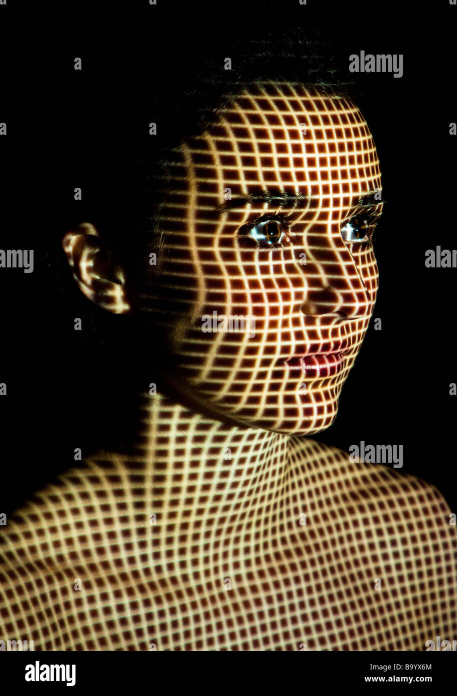 woman with profile patterns projected onto her face - Stock Image