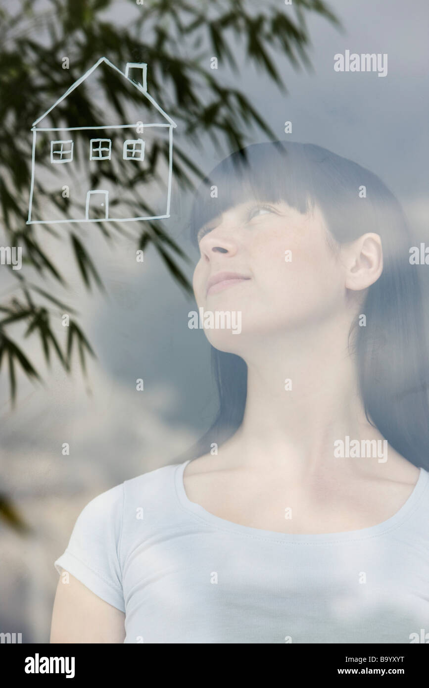 Young woman dreaming about a house - Stock Image