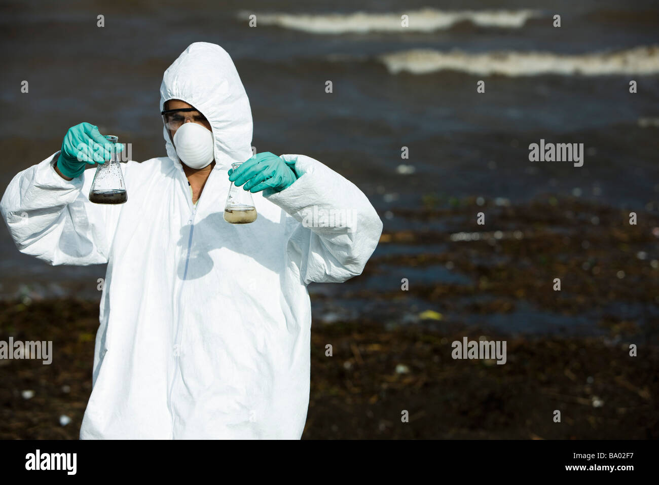 Person in protective suit testing polluted water - Stock Image