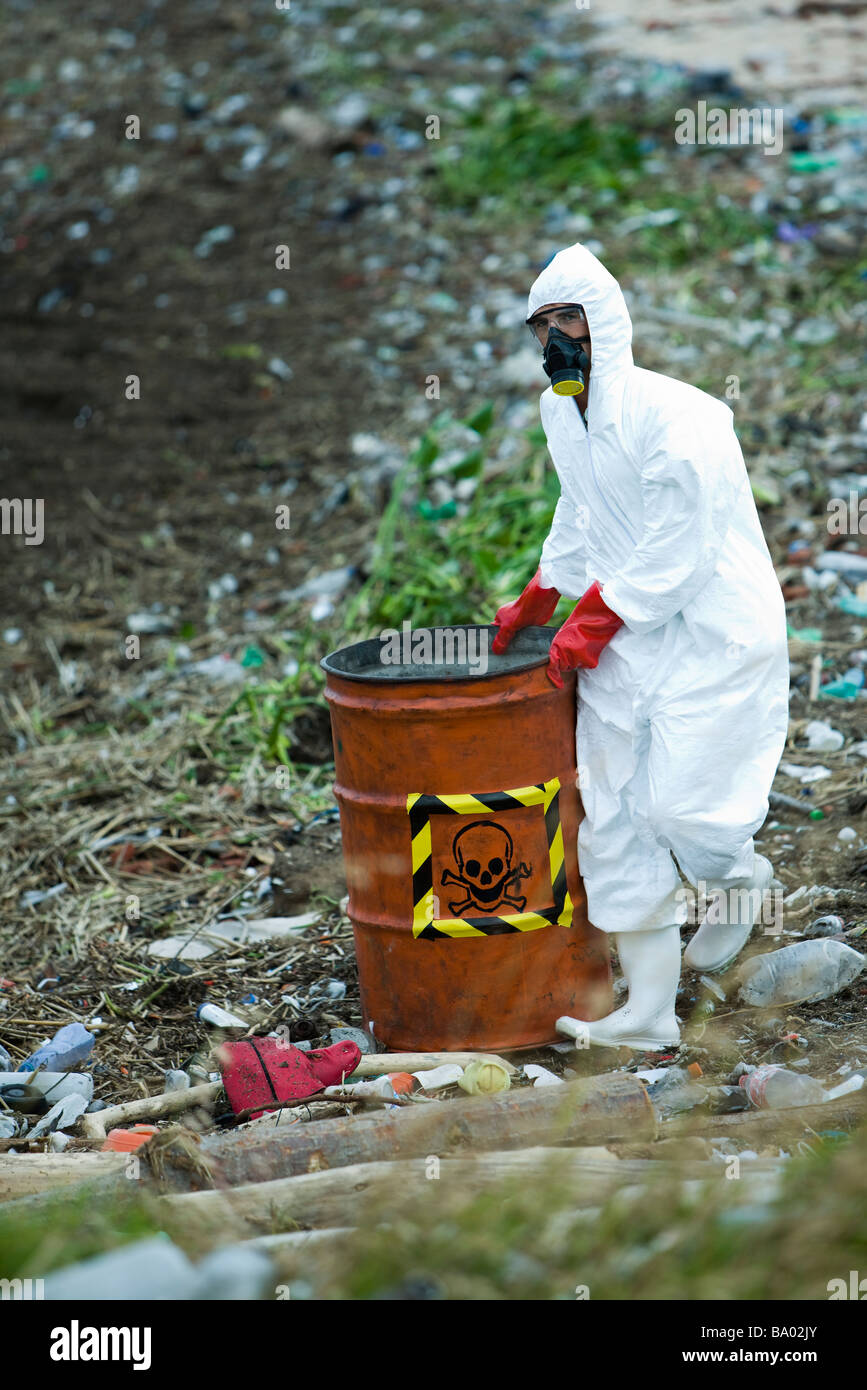 Person in protective suit carrying barrel of hazardous waste - Stock Image