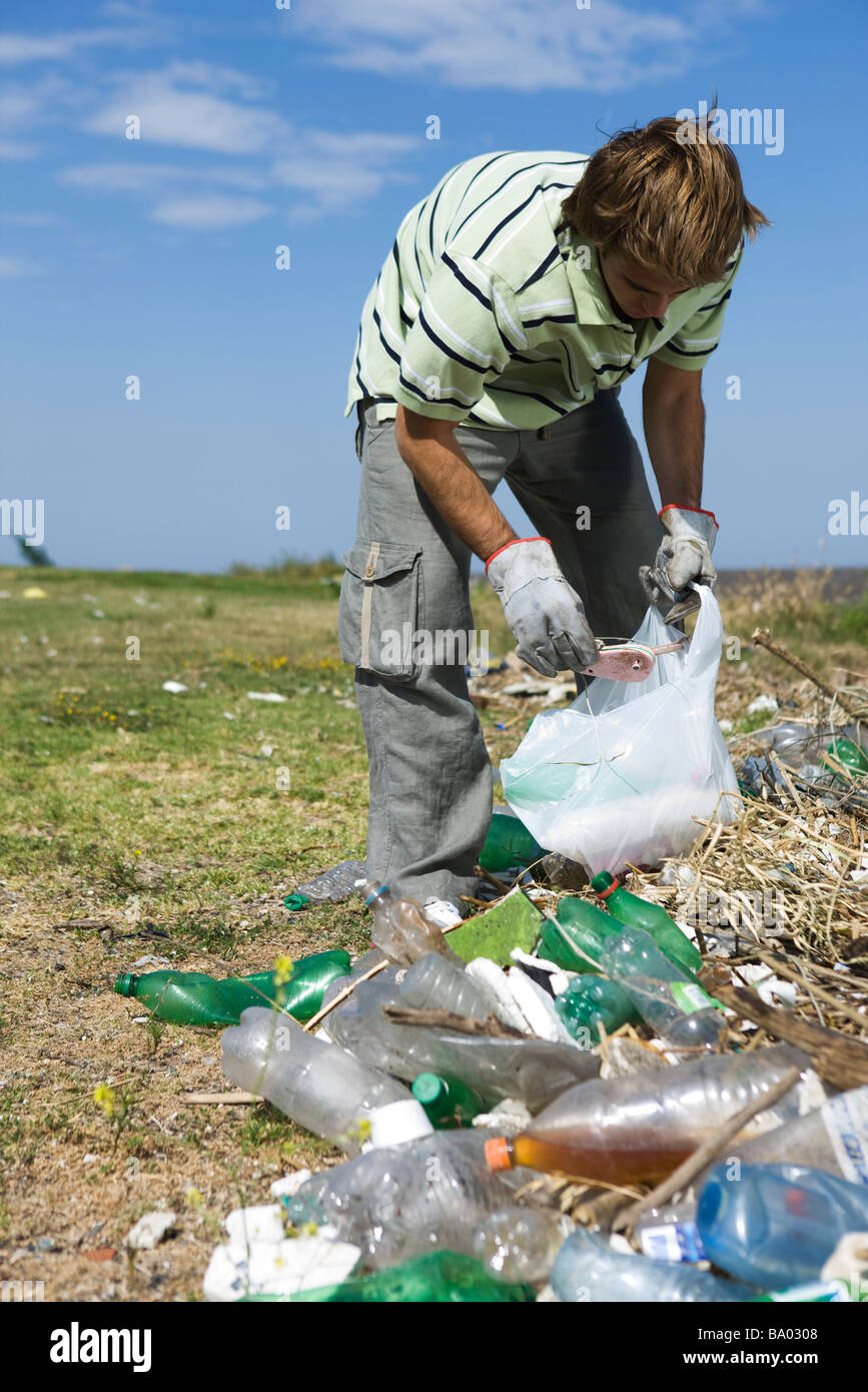 Male picking up trash in field Stock Photo