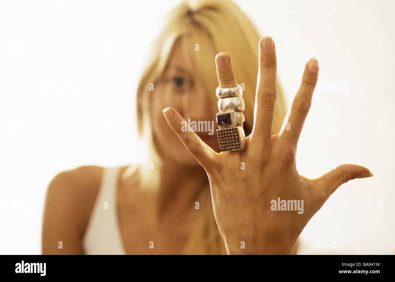 Woman showing many rings on her finger to camera - Stock Image