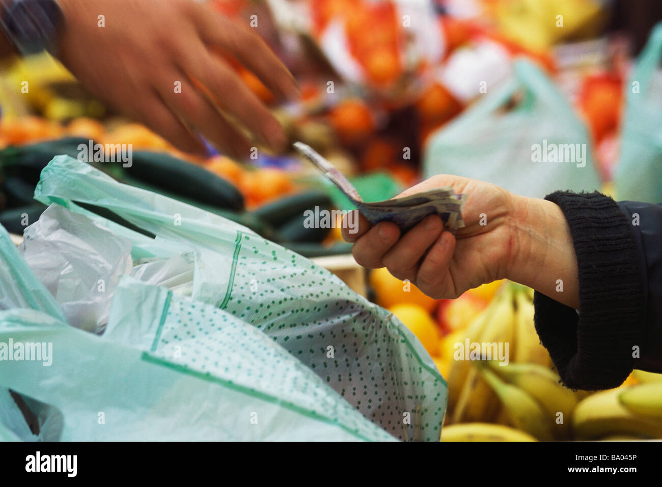 Person paying in market, cropped view - Stock Image