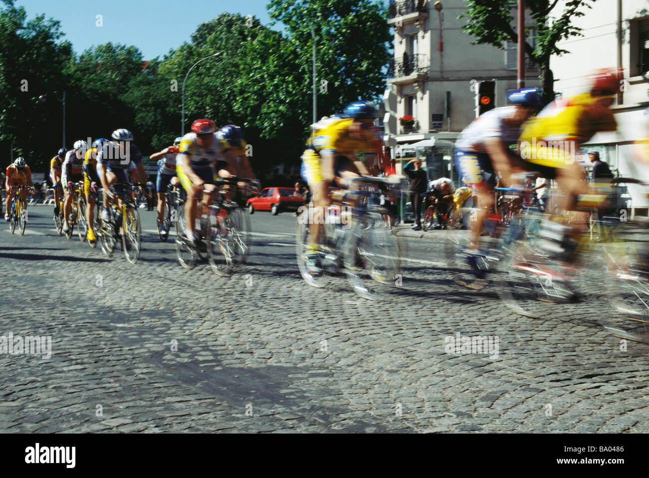 Cyclists racing on cobblestone street - Stock Image