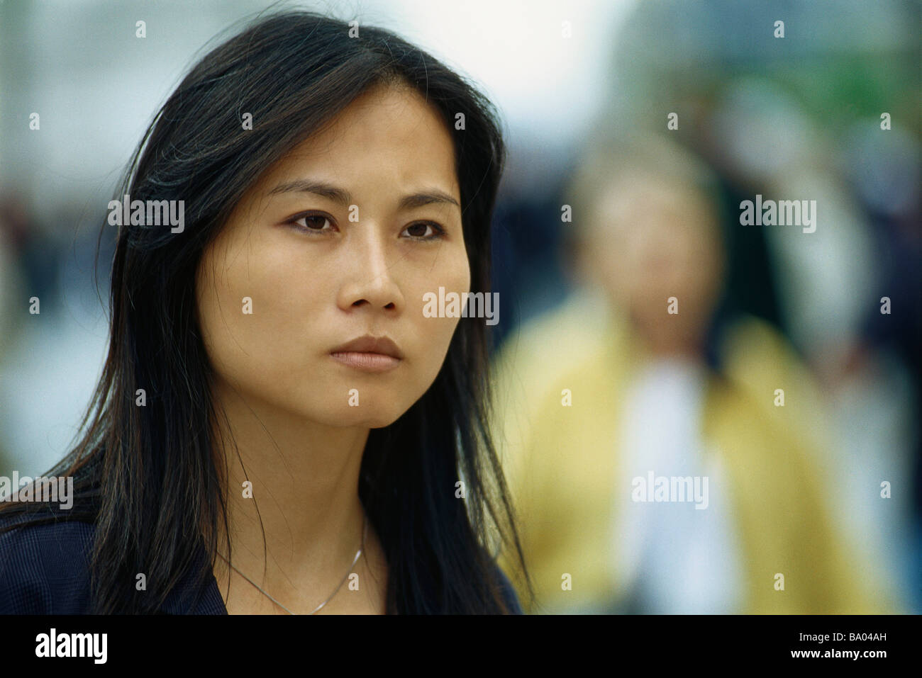 Woman looking away with brow furrowed - Stock Image