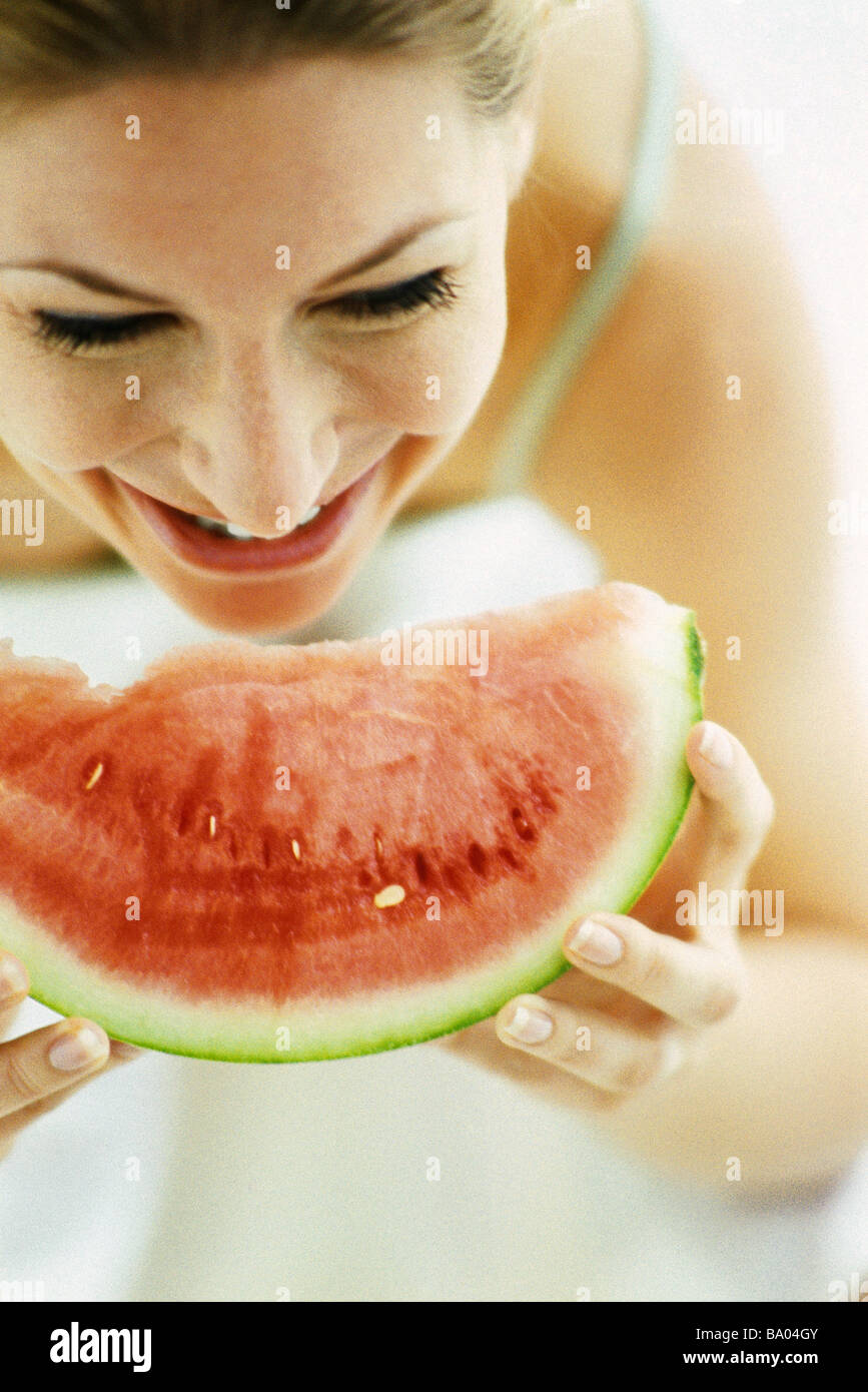 Woman eating slice of watermelon - Stock Image