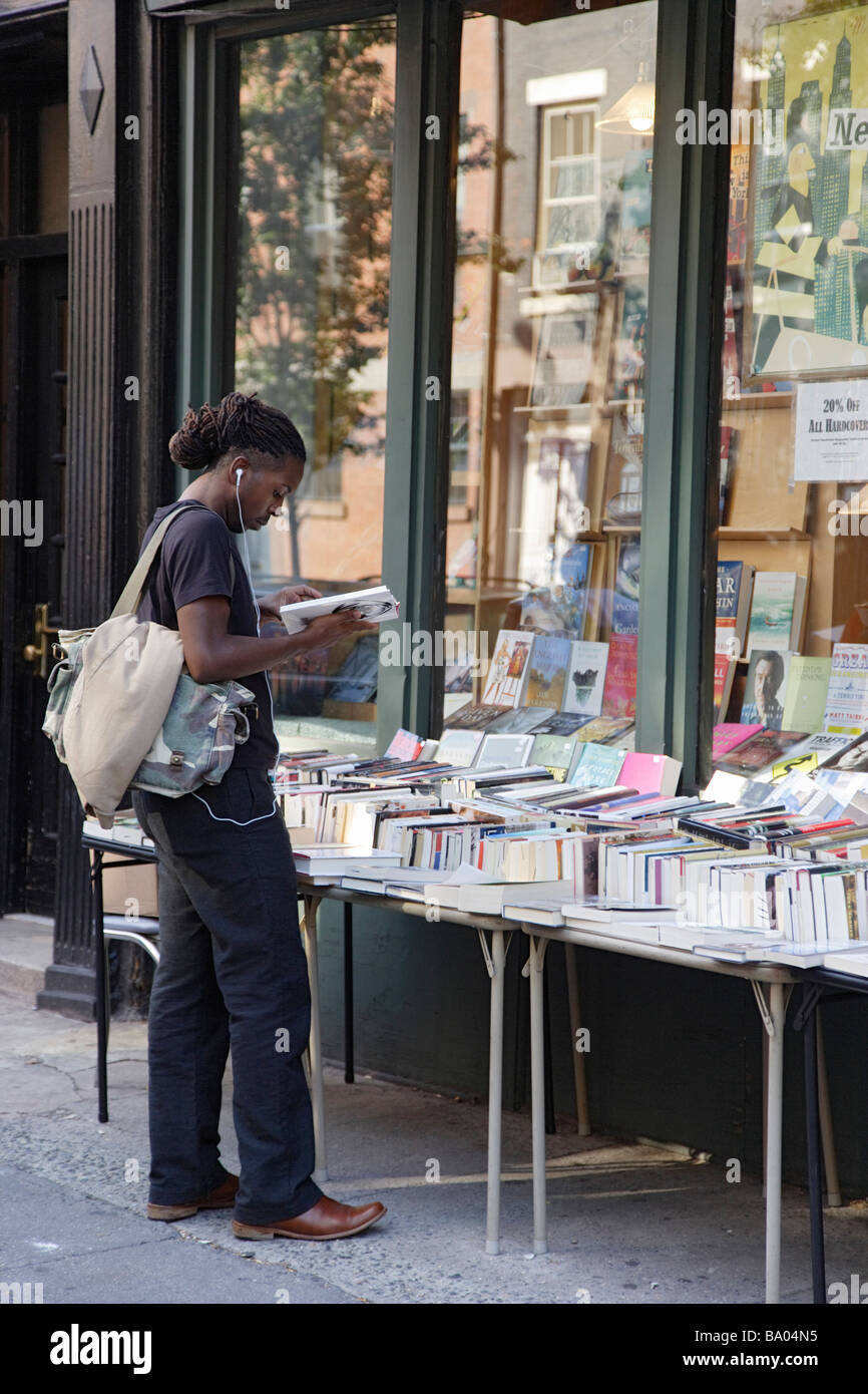 Young man in front of a bookshop Greenwich Village Manhattan New York City New York USA - Stock Image