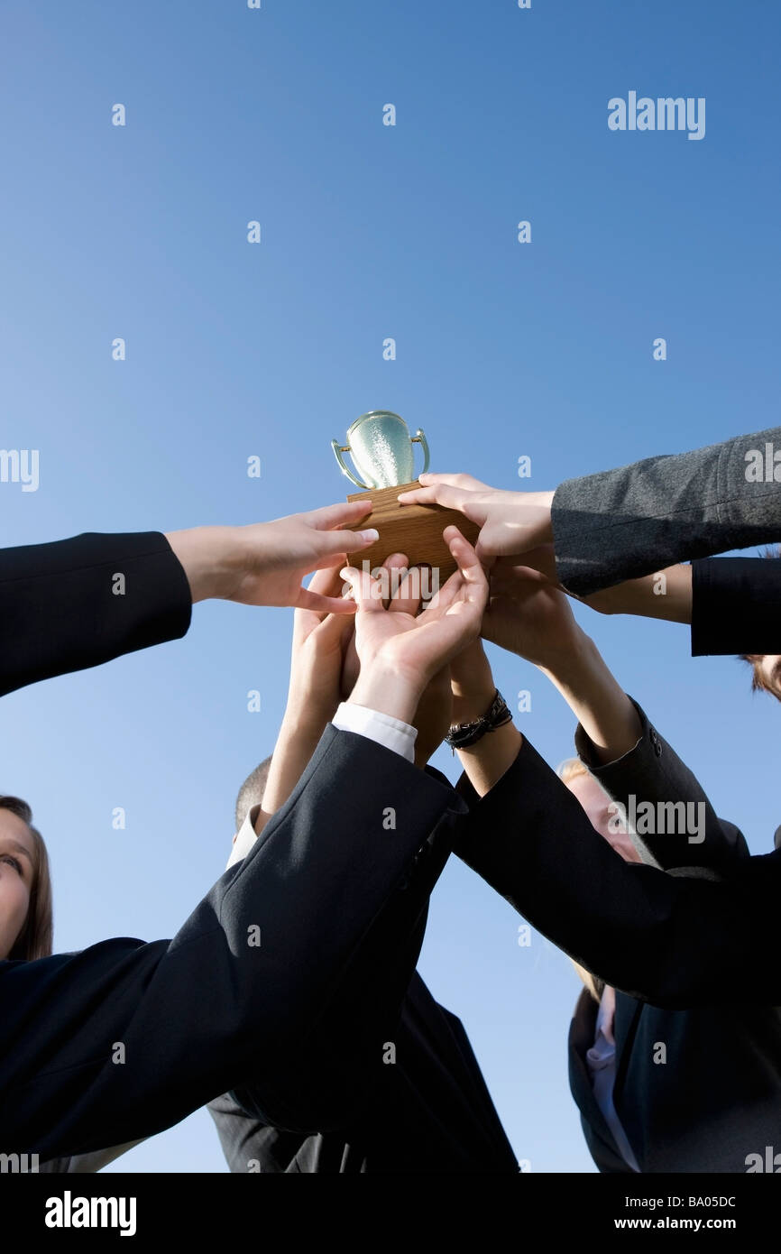 Group in business attire holding a trophy - Stock Image