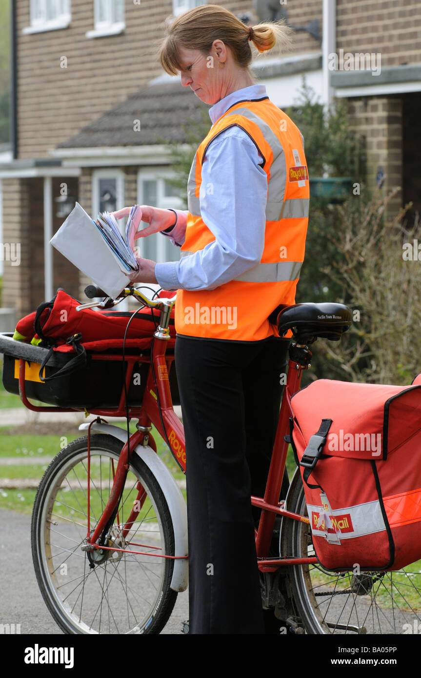 Royal Mail postwoman sorting letters on her round - Stock Image