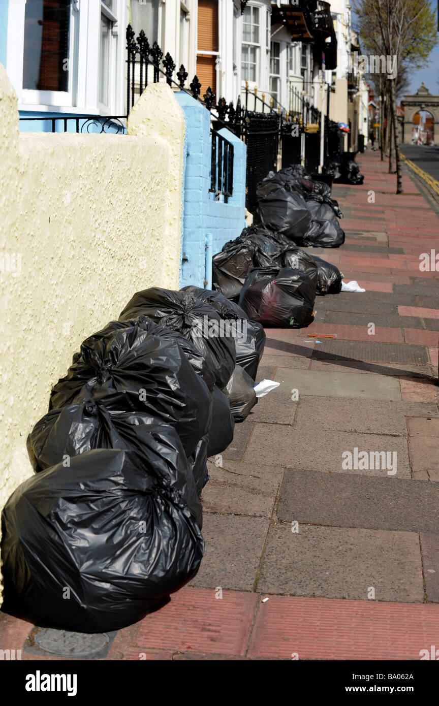 A line of black bin liner wait to be collected by bin men on rubbish collection day - Stock Image