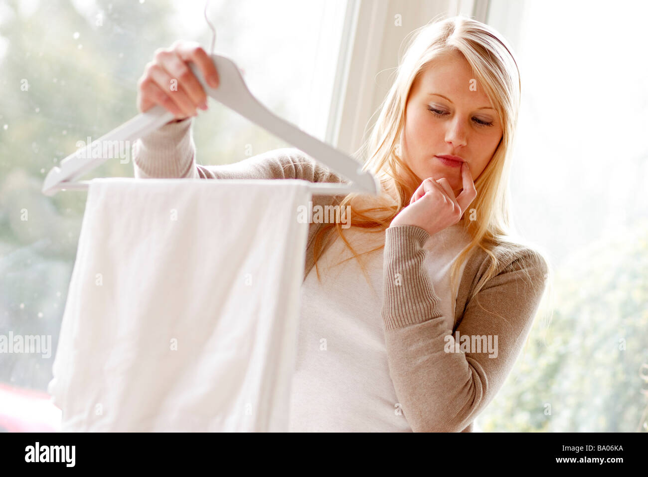 Woman looking at pants on hanger - Stock Image
