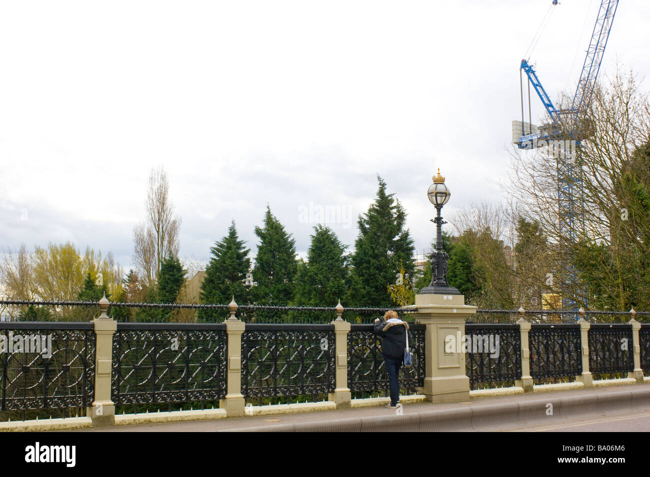 A pedestrian surveys the distant view of central London from victorian stone and cast iron infamous bridge in Highgate, - Stock Image