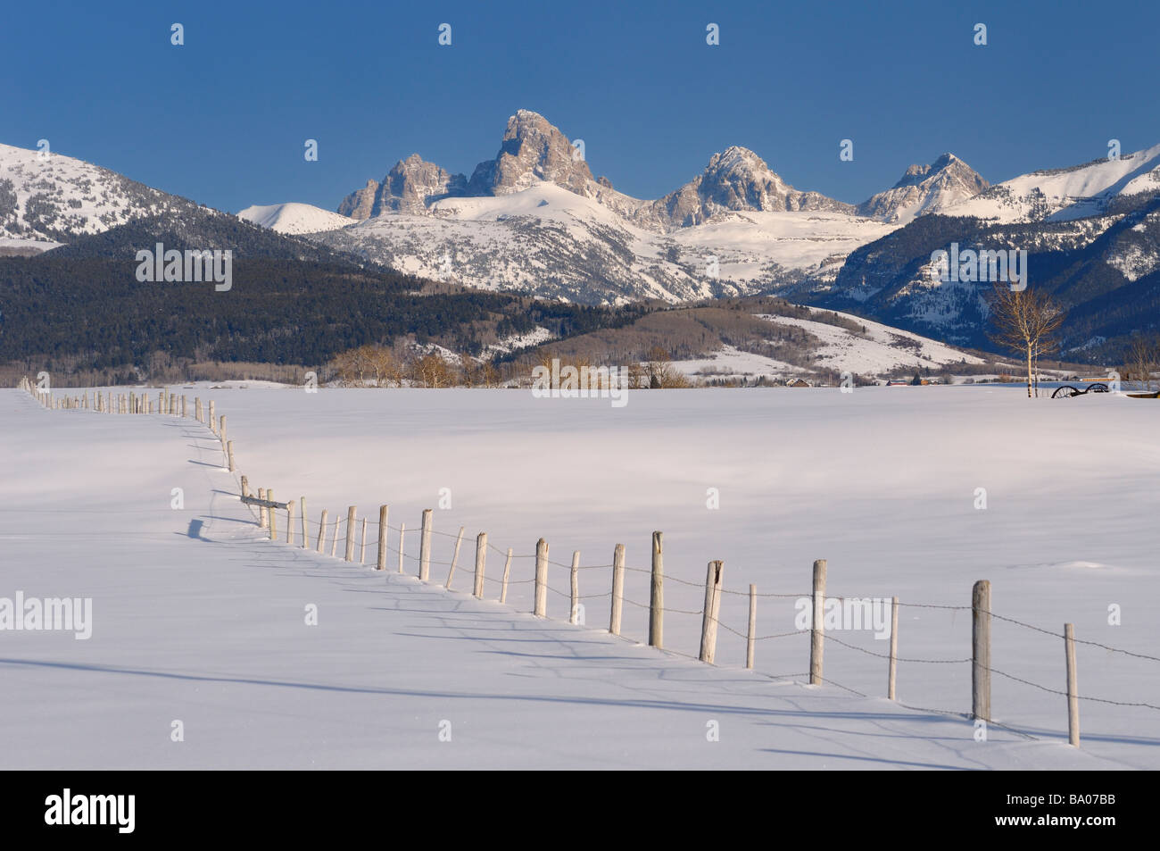 Mount Owen Grand Teton Middle Teton and South Teton in winter from Idaho with fence in snow covered field - Stock Image