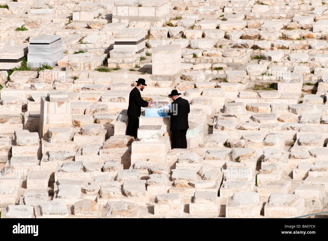 Orthodox Jews prying at one of the tombs in the cemetery on the Mount of Olives Jerusalem, Israel - Stock Image