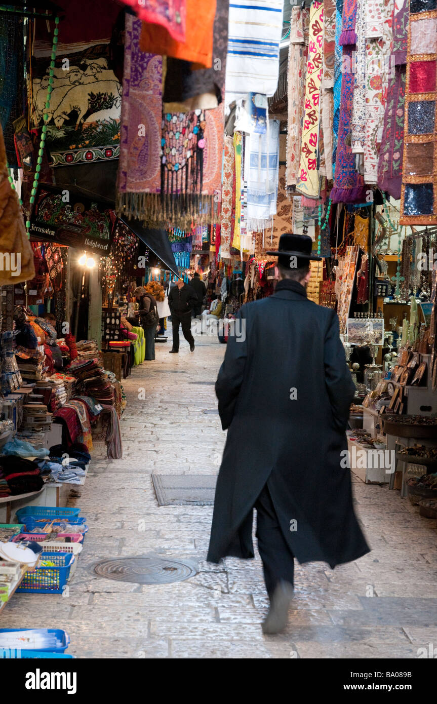 Orthodox Jew walking through a narrow street in the Arab Quarter of the Old City Jerusalem Israel - Stock Image