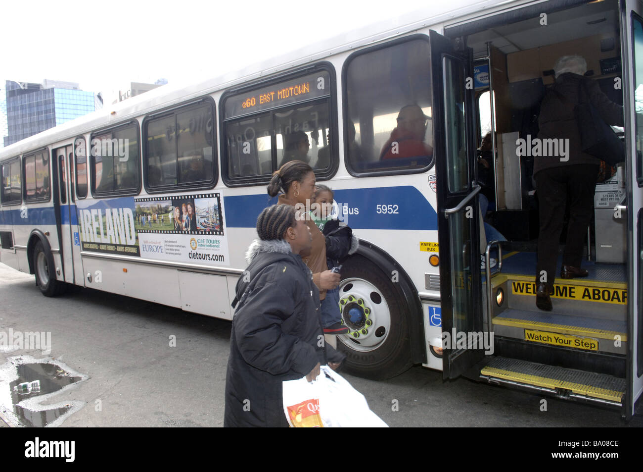 A family boards the B60 bus on Queens Boulevard in the New York borough of Queens Stock Photo