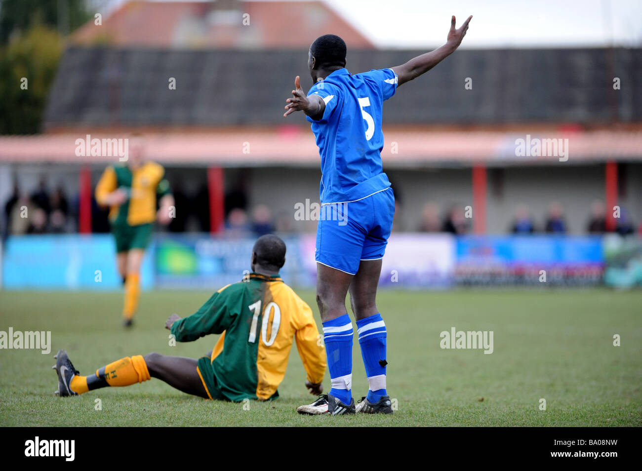 A footballer protests his innocence after another player is left on the ground after a tackle - Stock Image