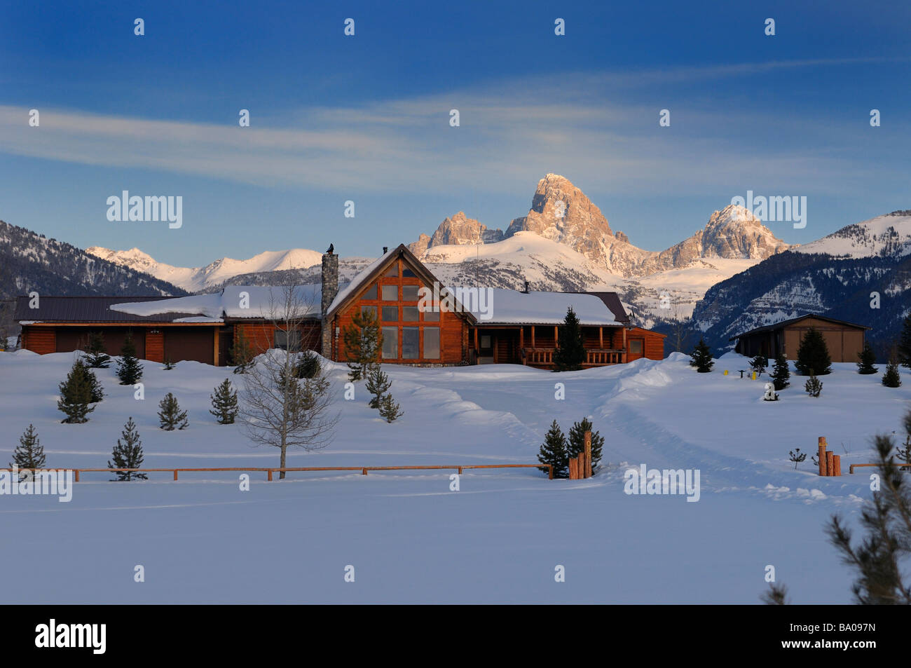 New house in winter evening in Idaho with Grand Teton peaks Wyoming in sunlight at sundown - Stock Image