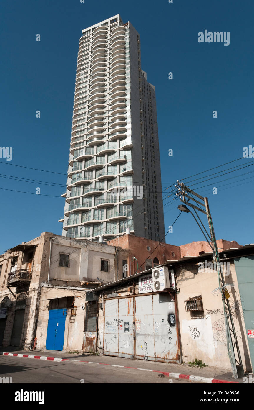 New high rise apartment building seen from a rundown part of town Tel Aviv Israel - Stock Image