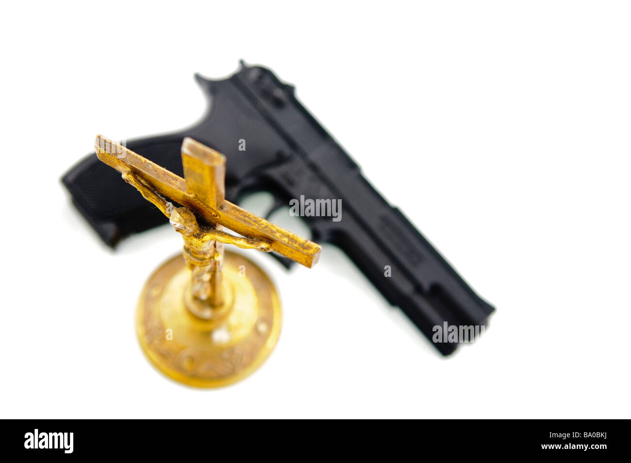Handgun beside an old brass crucifix NOTE Handgun is imitation toy and marked accordingly - Stock Image