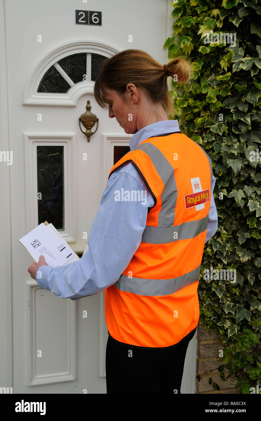 royal mail postwoman at the front door of a house delivering mail to a customer - Stock Image