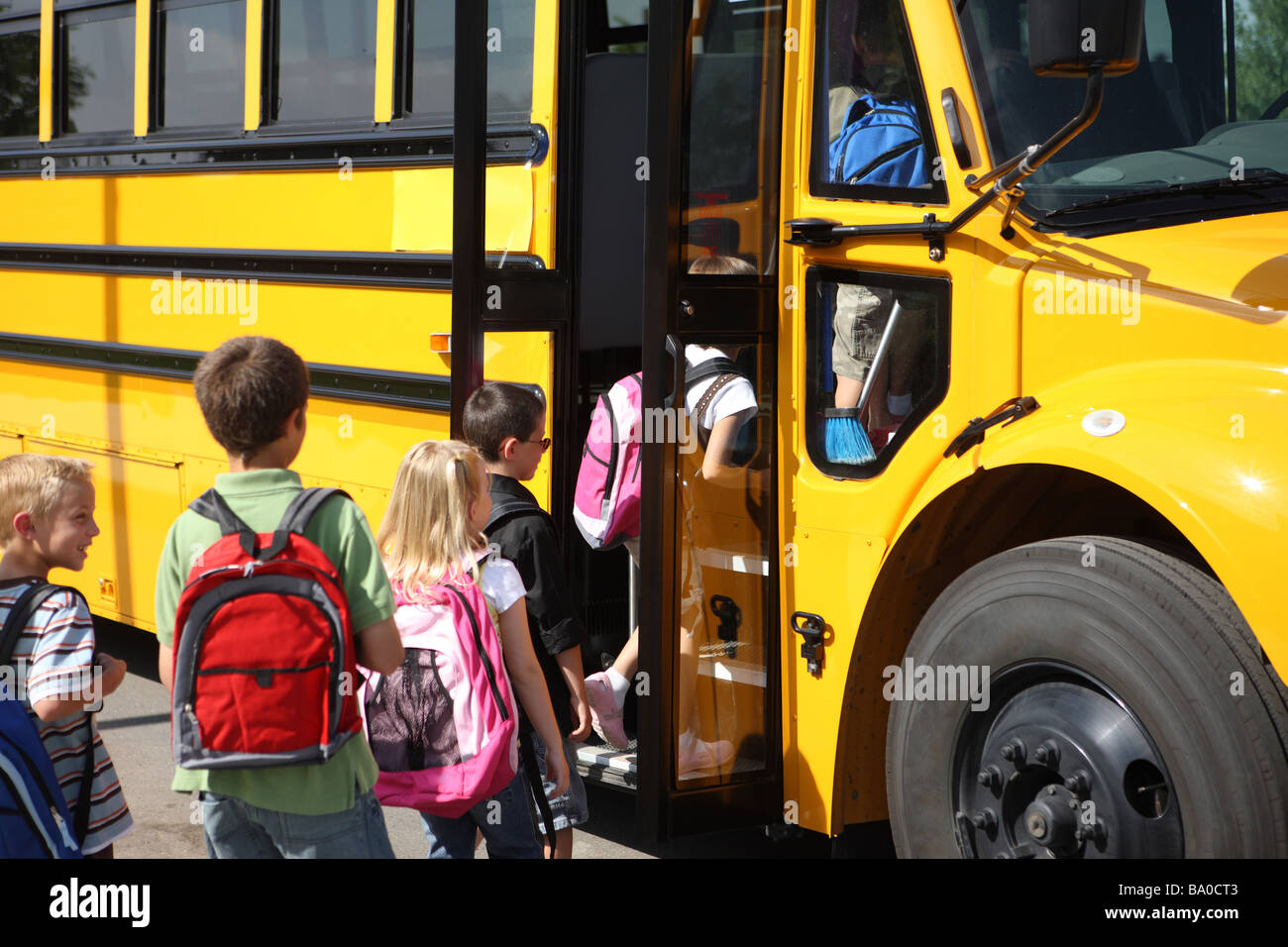 Children getting on school bus - Stock Image