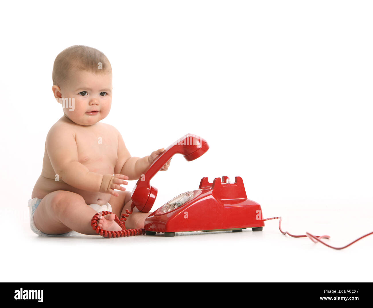 Baby with red telephone on white background - Stock Image