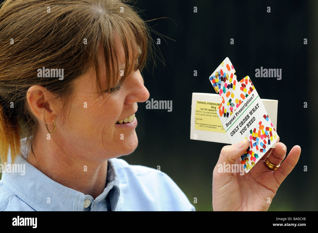 Repeat prescription then only order what tablets or medicine is required notice woman holding coloured card cutout - Stock Image