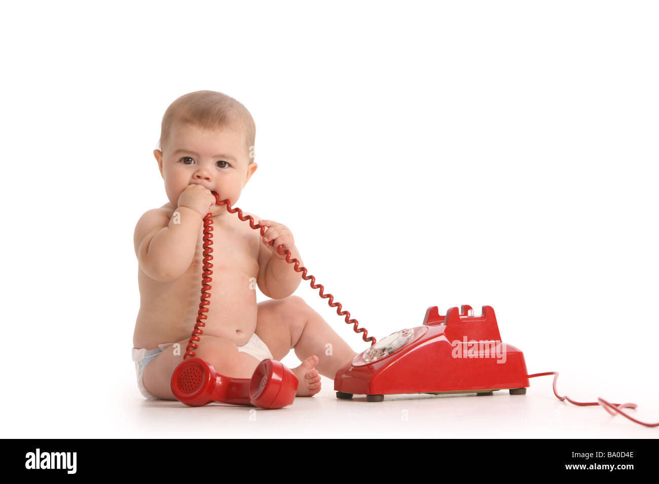 Baby with red phone on white background - Stock Image