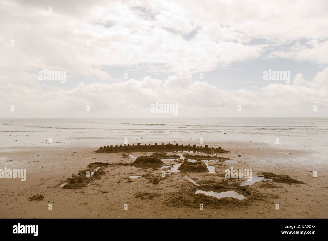 An elaborate sand castle with a network of moats and canals, on a beach under cloudy sky, and distant waves from - Stock Image