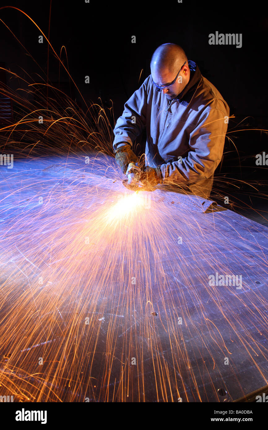 Sparks fly as man grinds metal - Stock Image
