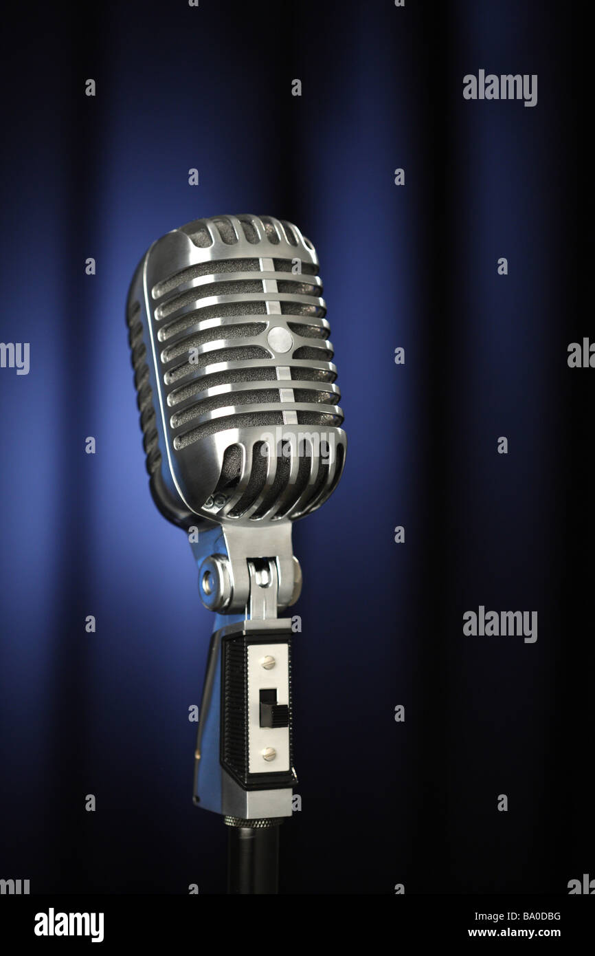 Vintage microphone with dark blue curtain background - Stock Image