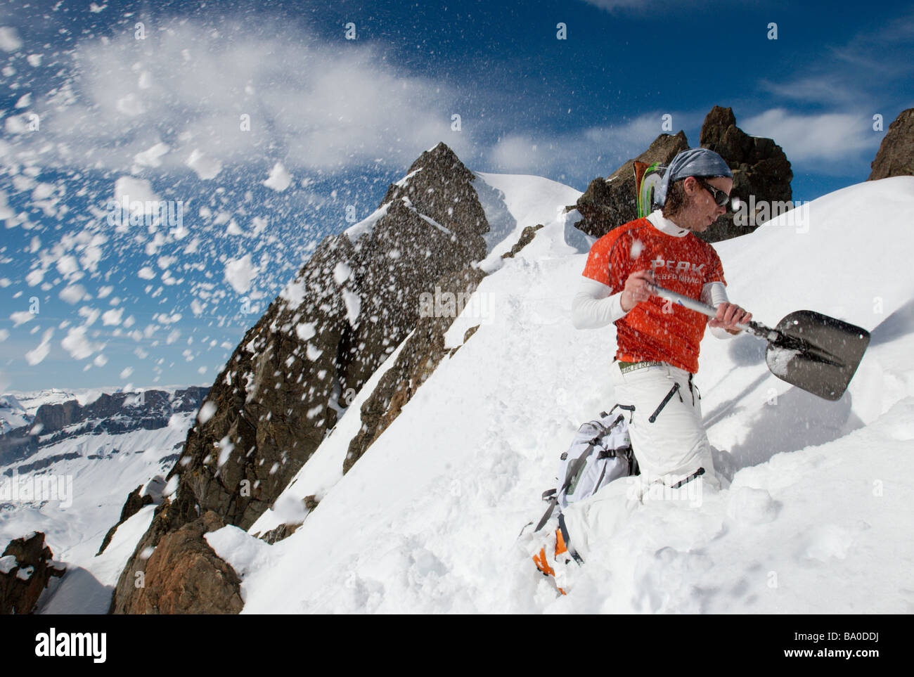 Skier digging snow in the mountains, Chamonix, France - Stock Image
