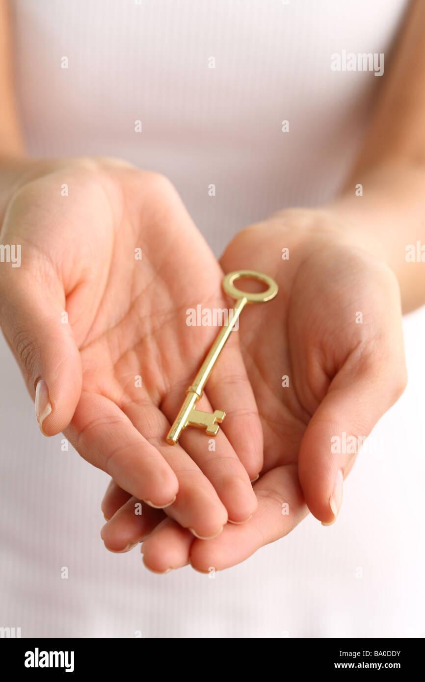Hands holding antique golden key - Stock Image