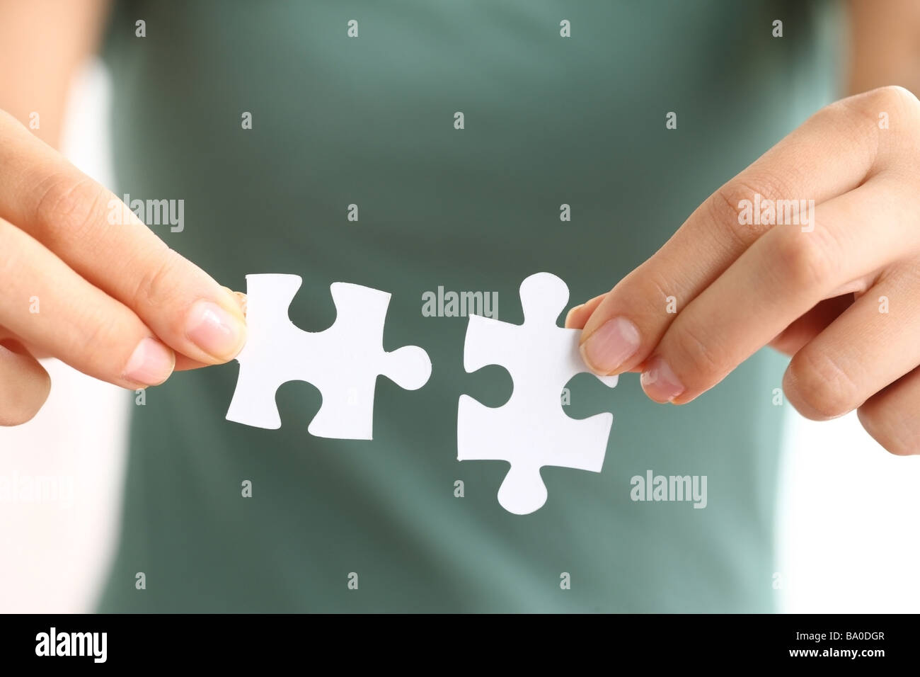 Hands holding two matching puzzle pieces - Stock Image
