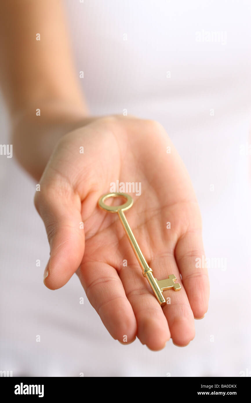 Antique gold key in hand - Stock Image