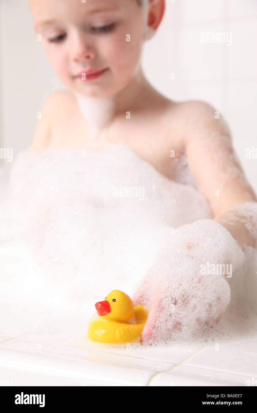 Young boy playing with rubber duckie in bath - Stock Image