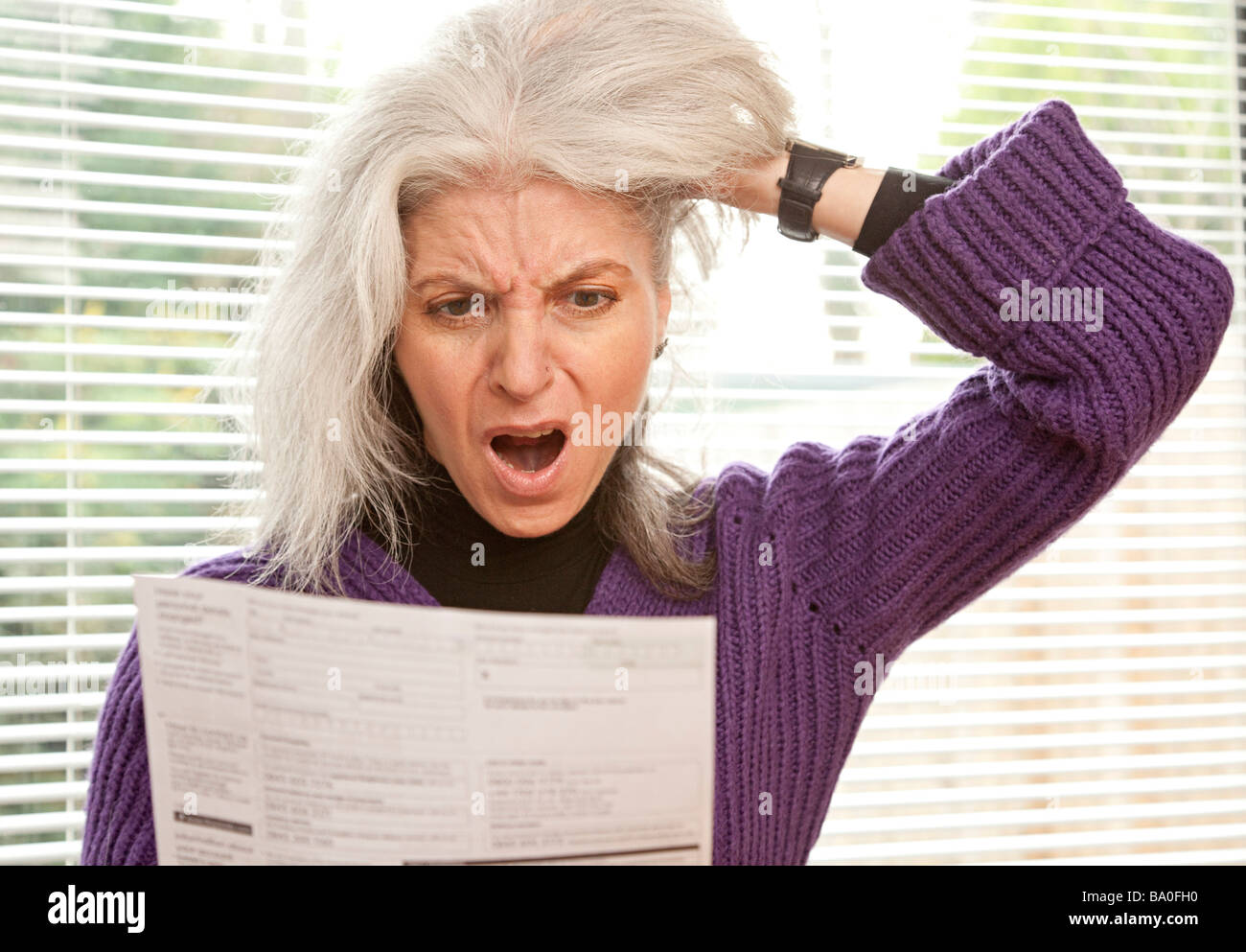 woman shocked at reading letter / bill / bank statement - Stock Image