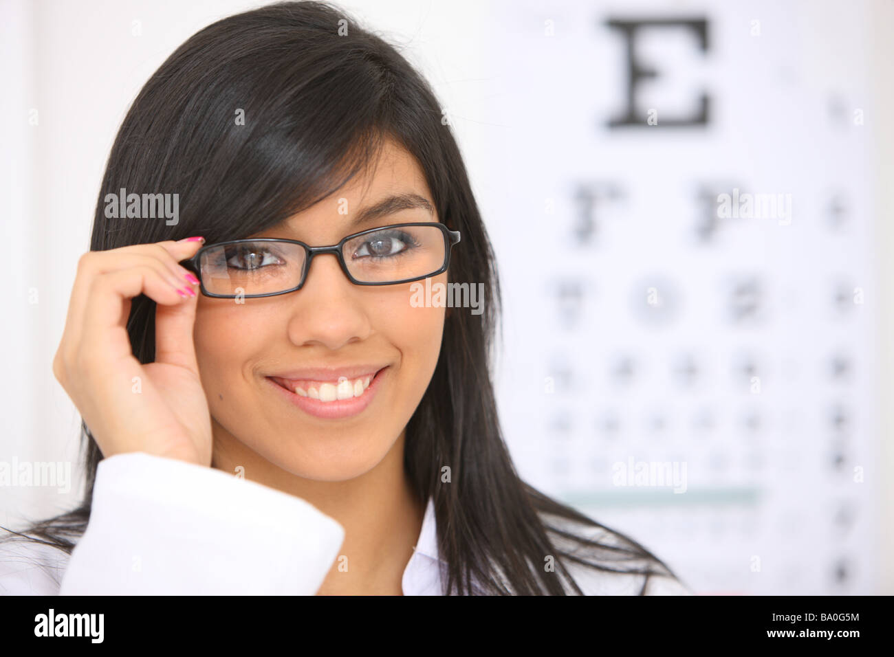 Young woman with glasses eye chart in background - Stock Image