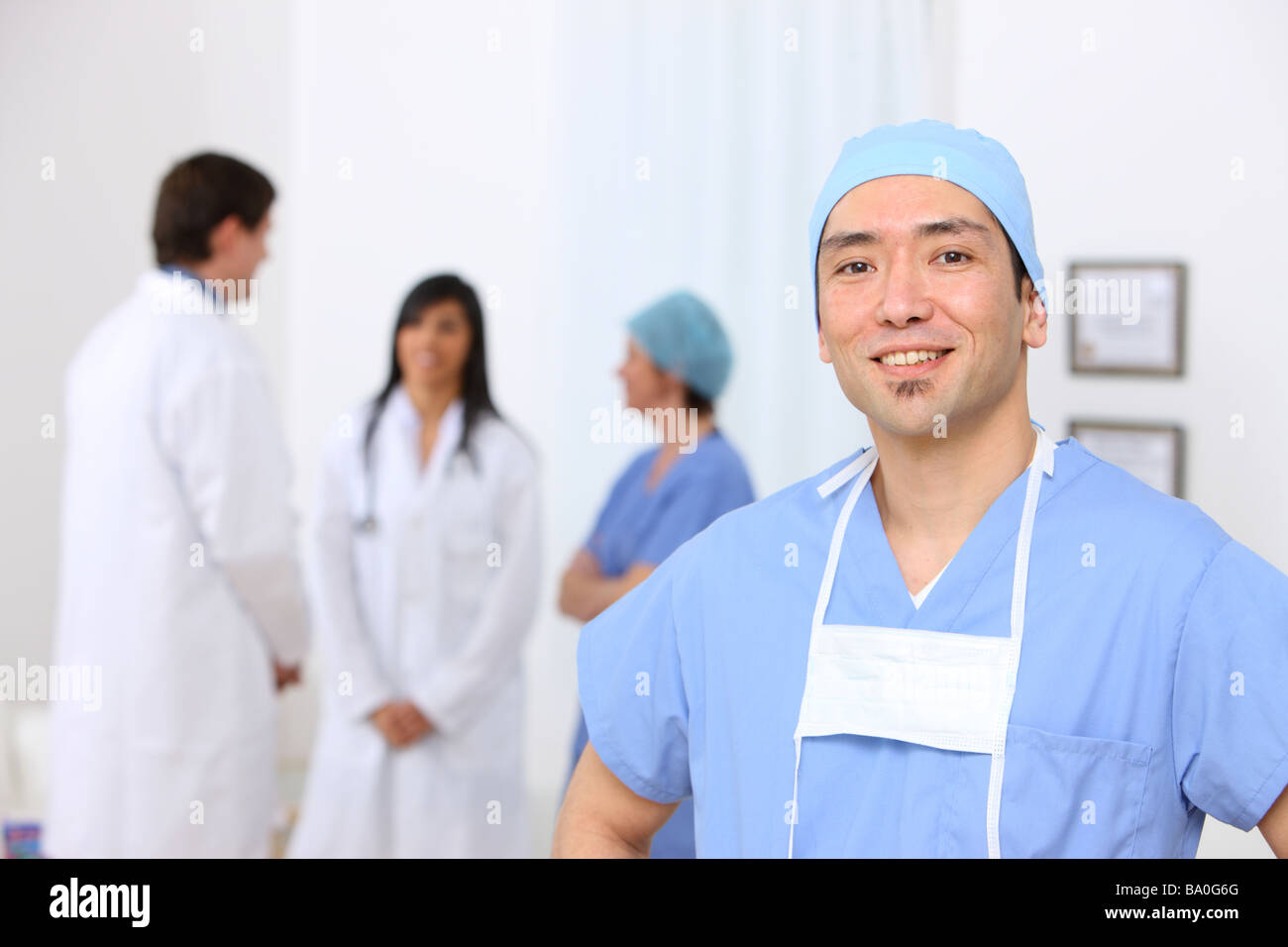 Portrait of surgeon with other medical personnel in background - Stock Image