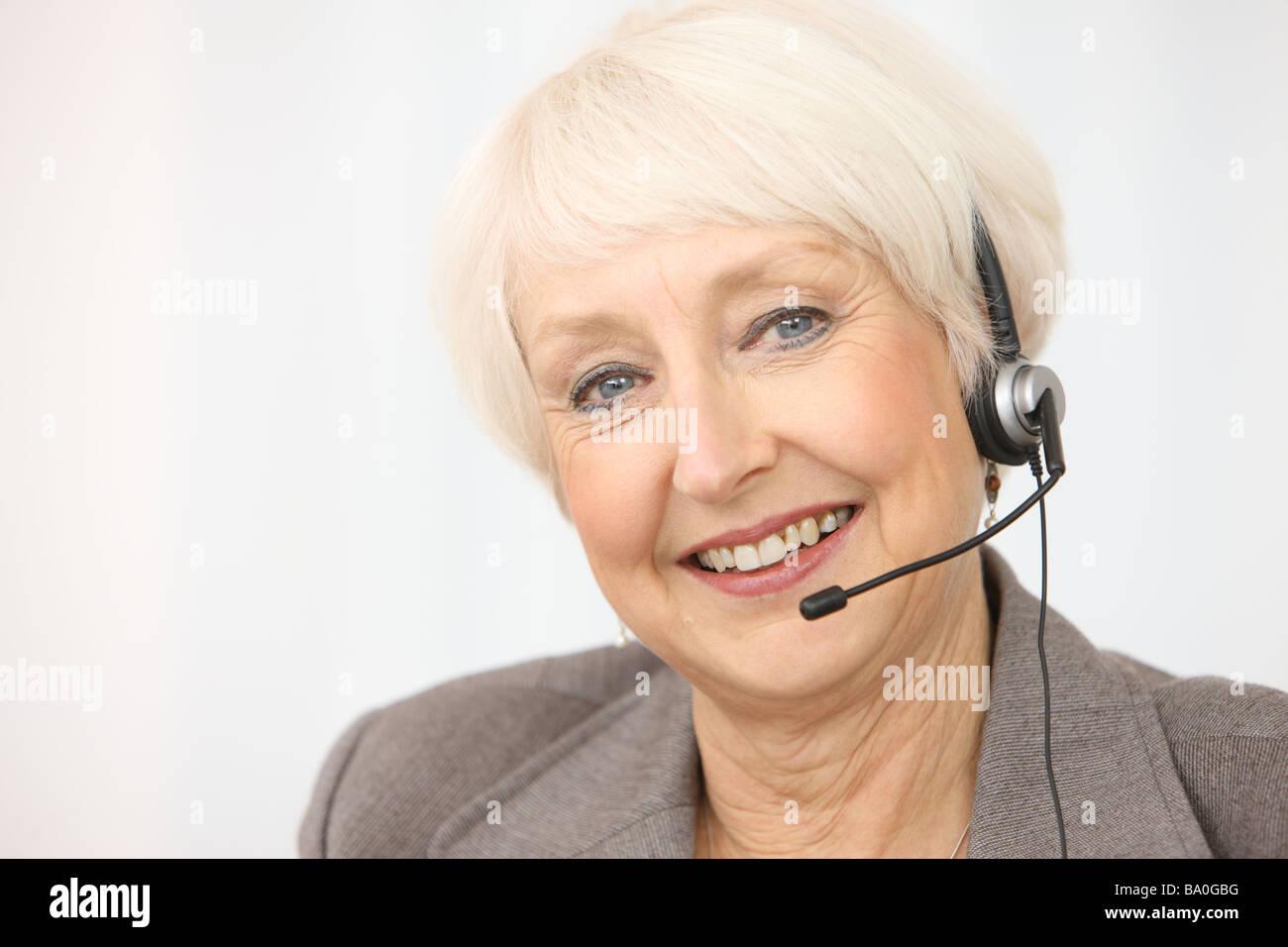 Professional senior businesswoman wearing headset - Stock Image