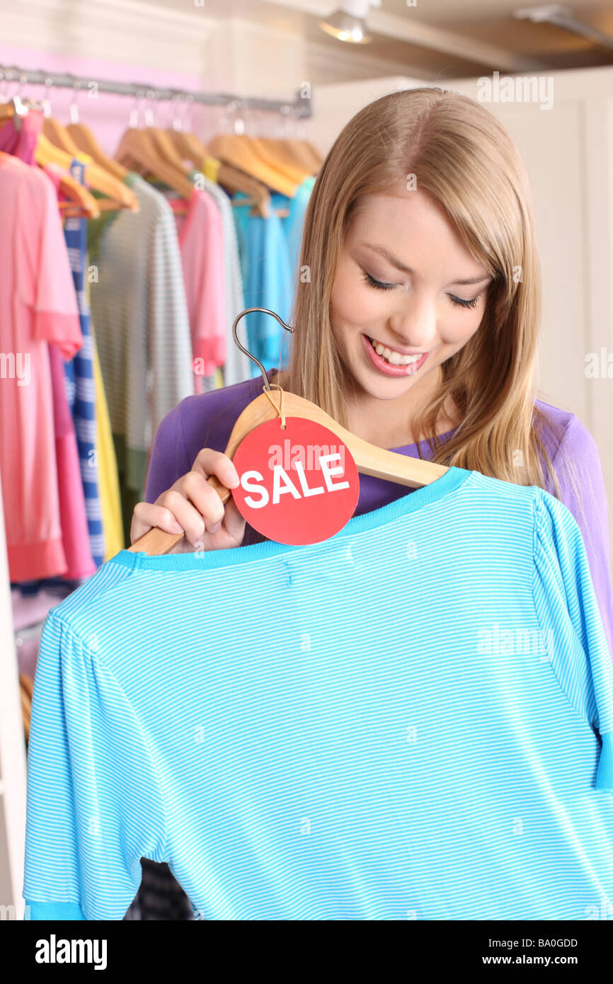 Teenage shopper looks at shirt with sale tag - Stock Image
