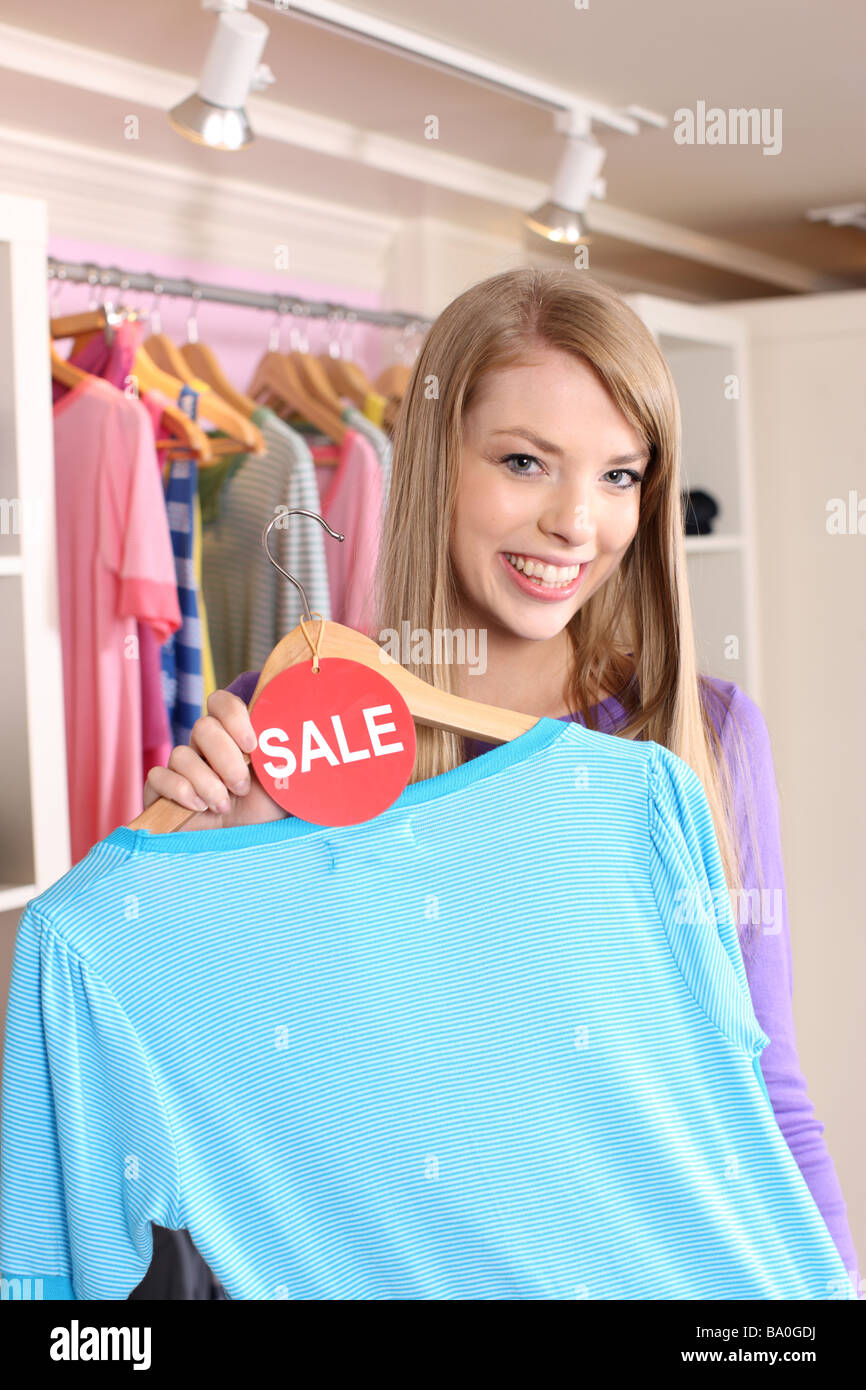 Young female shopper holding shirt with sale tag - Stock Image