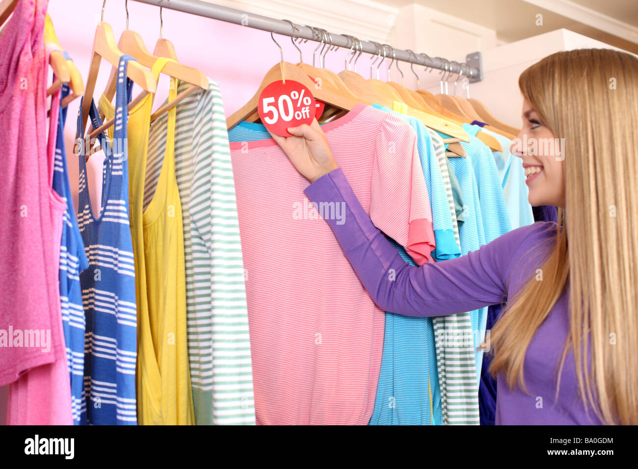 Young woman looking at clothing with sale tag - Stock Image
