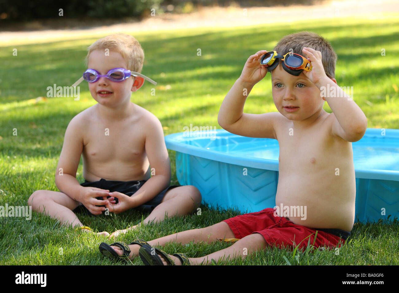 Two young boys sitting outside with goggles - Stock Image