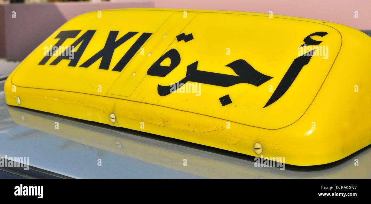Abu Dhabi close up of roof mounted yellow bilingual taxi cab sign United Arab Emirates Asia Stock Photo